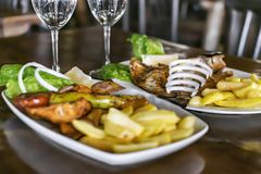 Traditional Mediterranean food. Two plates and glasses on the table in the restaurant. Baked fish and barbecue with vegetable. Garnish. View from above royalty free stock images