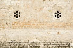 Traditional mediterranean stone wall with two small round stone windows royalty free stock photography