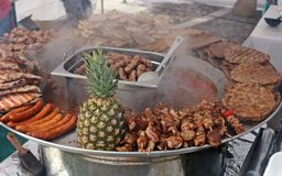 Traditional metal tray full of serbian street food with a pineapple in the middle. Traditional metal tray full of serbian street food. Among cevapcici royalty free stock images