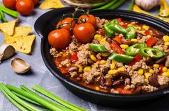 Traditional Mexican chili concarne. Traditional Mexican chili con carne on the table with vegetables and nachos. Selective focus Stock Photos