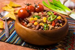 Traditional Mexican chili concarne. Traditional Mexican chili con carne on the table with vegetables and nachos. Selective focus Stock Photo