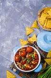 Traditional Mexican chili concarne. Traditional Mexican chili con carne on the table with vegetables and nachos. Selective focus Royalty Free Stock Image
