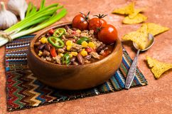 Traditional Mexican chili concarne. Traditional Mexican chili con carne on the table with vegetables and nachos. Selective focus Royalty Free Stock Photo