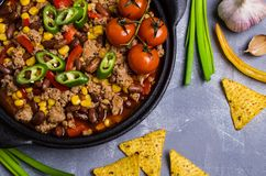 Traditional Mexican chili concarne. Traditional Mexican chili con carne on the table with vegetables and nachos. Selective focus Royalty Free Stock Images