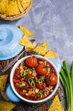 Traditional Mexican chili concarne. Traditional Mexican chili con carne on the table with vegetables and nachos. Selective focus Stock Photography