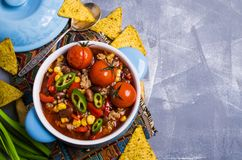 Traditional Mexican chili concarne. Traditional Mexican chili con carne on the table with vegetables and nachos. Selective focus Royalty Free Stock Photography