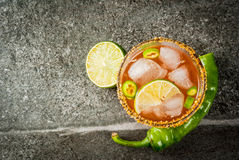 Traditional Mexican cocktail Spicy michelada. Alcohol. Traditional Mexican South American cocktail. Spicy michelada with hot jalapeno peppers and lime. On a dark Stock Photo
