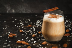 Traditional Mexican drink Horchata Latte. Coffee mixed with Horchata, a cocktail of almonds, rice  vanilla and cinnamon. On a black concrete table, with Royalty Free Stock Images
