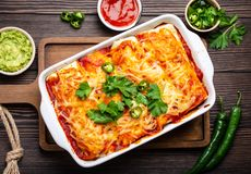 Traditional Mexican enchiladas. Traditional Mexican dish enchiladas with meat, chili red sauce and cheese in white casserole dish over rustic wooden background royalty free stock photos