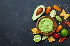 Traditional mexican food. Bowl guacamole sauce with avocado, lime and nachos on black table top view. Copy space for recipe. stock photo