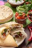 Traditional Mexican food. Cilantro and lime rice, chicken fajitas, fajita peppers, burritos, tortillas, guacamole and salsa Stock Image