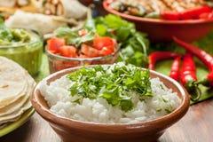 Traditional Mexican food. Cilantro and lime rice, chicken fajitas, fajita peppers, burritos, tortillas, guacamole and salsa stock images