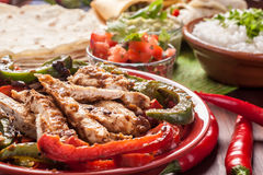 Traditional Mexican food. Ingredients: chicken fajitas, fajita peppers, cilantro and lime rice,  tortillas, guacamole and salsa Royalty Free Stock Image