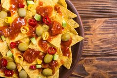 Nachos with sauce salsa. Traditional mexican food . Nachos with sauce salsa , olives , chili peppers and avocado stock images