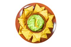 Traditional Mexican Guacamole sauce made from avocado and lime chips nachos on a white background. Guacamole and nachos isolated o. N white background. Top view royalty free stock photo