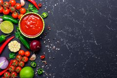Traditional Mexican Latin American salsa sauce and ingredients on black stone table. Top view copy space. Traditional Mexican Latin American salsa sauce on black royalty free stock image