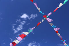 Traditional mexican paper bunting decoration celebratory flags against blue sky. Festive flags against blue sky and tree Royalty Free Stock Photos