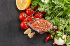 Traditional mexican red spicy sauce salsa with ingredients. On the gray slater background. Copyspace Stock Photos