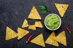 Traditional Mexican snack of guacamole and corn chips on black background.  stock photo