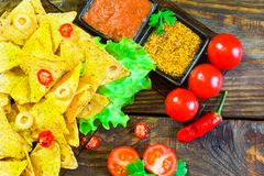 Nachos top view with Tortilla chips tomato salsa and mustard on rustic wooden background. A textured background.Copy paste place Stock Photos