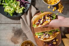 Traditional mexican taco with chicken and vegetables on wooden table. Latin american food.  royalty free stock photo