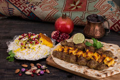 Traditional Middle eastern Persian chicken and lamb meat Shashlik Kebab skewered meat BBQ Grill on flat pita bread and saffron r. Ice and tahchin and pomegranate royalty free stock photo