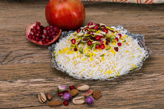 Traditional Middle eastern Persian saffron rice and tahchin, nuts and pomegranate on a wooden background. Royalty Free Stock Photo