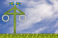 Traditional midsummer maypole in a field in Sweden. Illustration of a maypole with Swedish flags and wreaths with daisies on a green field with dandelion Stock Photography