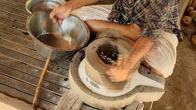 Woman sat cross-legged using hand-turned millstone to grind wet rice for making soaked rice flour