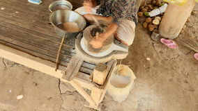 Upper view on woman sat cross-legged using hand-turned millstone to grind wet rice for making soaked rice flour