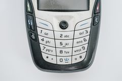 Traditional mobile phone in second generation with keyboard button and mini black and white monitor by white isolate die cut backg stock image