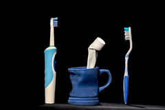Traditional and modern toothbrush. With pitcher with toothpaste isolated on black background/oral hygiene Stock Photo