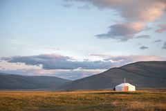 Traditional Mongolian ger on a mountain backdrop in sunset light. A single traditional family ger in warm afternoon light. Khuvsgol, Mongolia Royalty Free Stock Photography