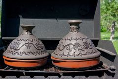 Traditional Moroccan ceramic tajine or tagine pot on a black grill sunny summer day stock images