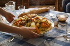 Family gathering around a couscous table concept. Traditional Moroccan homemade Couscous plate on a blue squared clothed table served by dynamic woman hands royalty free stock image