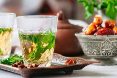 Traditional moroccan mint tea with dates on a vintage tray. Whit. E stone background Stock Photo