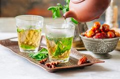 Traditional moroccan mint tea with dates on a vintage tray. Whit. E stone background Stock Photos