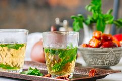 Traditional moroccan mint tea with dates on a vintage tray. Whit. E stone background Royalty Free Stock Images