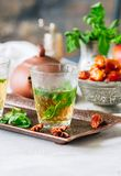 Traditional moroccan mint tea with dates on a vintage tray. Whit. E stone background Royalty Free Stock Photography