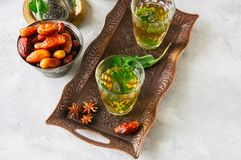 Traditional moroccan mint tea with dates on a vintage tray. Whit. E stone background Royalty Free Stock Image