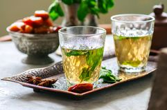 Traditional moroccan mint tea with dates on a vintage tray. Whit. E stone background Stock Image