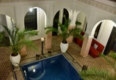 Traditional Moroccan riad interior with a pool. Authentic Moroccan riad with open courtyard and interior garden with a pool in the evening Stock Images
