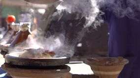 Traditional moroccan Tajine food cooking in Tajine pots on the fire with smoke and tomatoes on top. Hand of local Cook