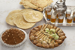 Traditional Moroccan tea at id-al-fitr the end of Ramadan. Traditional Moroccan tea,cookies, almond sellou and pancakes at id-al-fitr the end of Ramadan Royalty Free Stock Images
