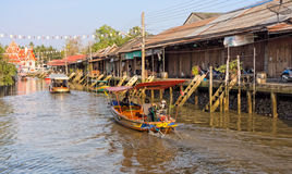The traditional motorboat and riverside Thai village Royalty Free Stock Photo