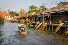 The traditional motorboat and riverside Thai village Royalty Free Stock Photos