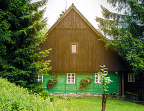 Traditional mountain chalet, brown and green front. Traditional mountain chalet, cottage or hut made of wood surrounded by spruce trees, painted green and brown Stock Photos
