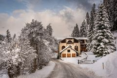 Traditional mountain chalet in snowy landscape royalty free stock image
