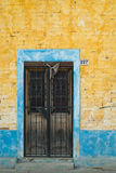 Traditional mourning bow above mexican door. Traditional black mourning bow above mexican door on house with warm colours Royalty Free Stock Images