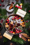 Traditional mulled wine in aged copper cooking pot with cranberries, cinnamon sticks, sliced orange and anise star on dark rusti Stock Photography